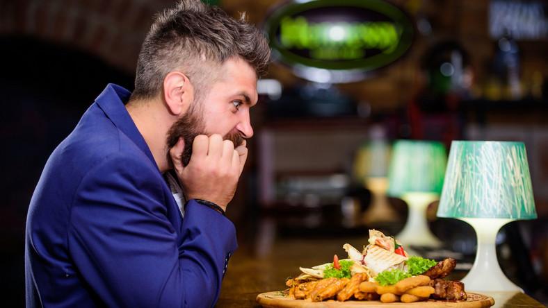 Głodny mężczyzna siedzi przed pełnym talerzem