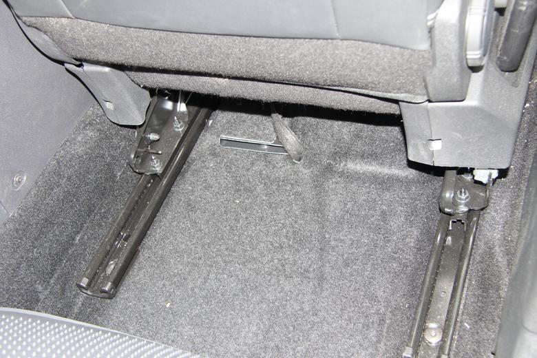 Subwoofer pod fotelem pasażera - schowany pod tapicerką. Widoczny fragment wiązki połączeniowej.