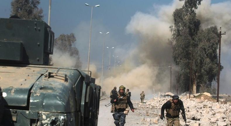 Smoke billows in the background as Iraqi forces advance on Mosul airport during an offensive to retake the western side of the city from jihadists of the Islamic State group on February 23, 2017