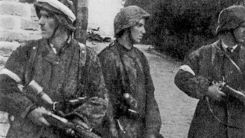 """Patrol z II plutonu """"Alek"""" 2. kompanii """"Rudy"""" batalionu """"Zośka"""" 5 sierpnia 1944 r. na Gęsiówce. Od lewej stoją: Wojciech Omyła """"Wojtek"""", Juliusz Bogdan Deczkowski """"Laudański"""" i Tadeusz Milewski """"Ćwik"""". Milewski poległ na terenie """"Gęsiówki"""" w dniu zrobienia tego zdjęcia; Omyła zginie trzy dni później. W chwilę po zrobieniu tego zdjęcia, w mur nad głowami powstańców uderzył niemiecki pocisk karabinowy - nikomu nic się nie stało"""