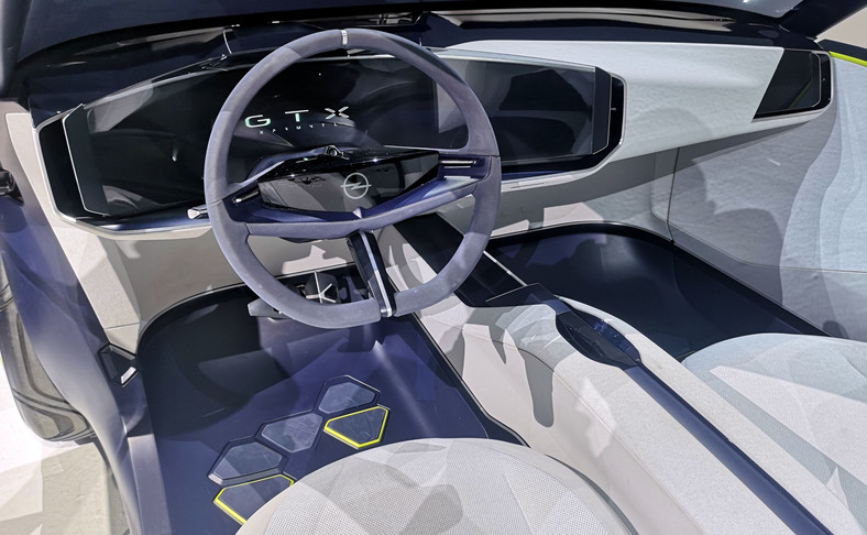 Opel GT X Experimental.Uproszczona stylistyka kierownicy - jej środkowy moduł nawiązuje kształtem do Opel Vizor. Diodowe logo marki pozostaje nieruchome niezależnie od położenia wieńca. Nam jej wygląd przypomina kierownice stosowane w modelach z lat 60. i 70. ubiegłego wieku - wtedy Ople Kapitan, Admiral i Diplomat (seria KAD) były najbardziej prestiżowymi modelami w ofercie marki. Czy takie bajery dostanie NOWA Mokka?