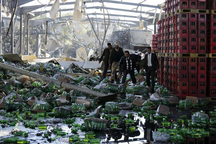 Officials inspect damage at a Coca-Cola beverages factory after Saudi-led air strikes destroyed it i