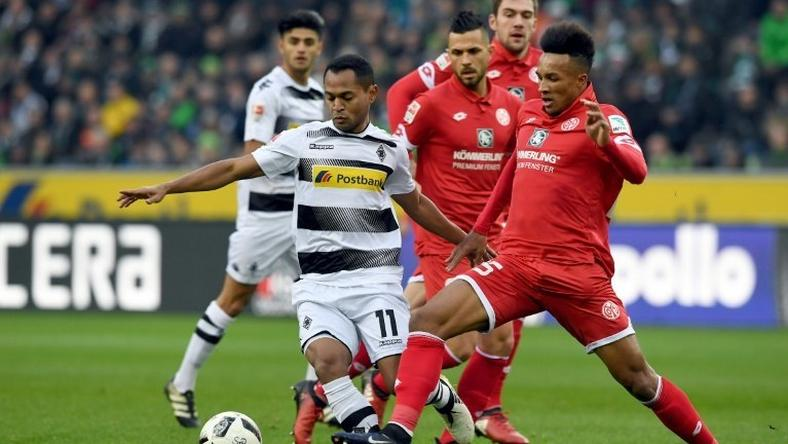 Moenchengladbach's forward Raffael (L) and Mainz' midfielder Jean Philippe Gbamin fight for the ball during their Bundesliga match in Moenchengladbach, on December 11, 2016