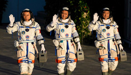 Left to right: Tang Hongbo, Nie Haisheng, and Liu Boming wave as they prepare to board for liftoff at the Jiuquan Satellite Launch Center in Jiuquan in northwestern China, June 17, 2021.