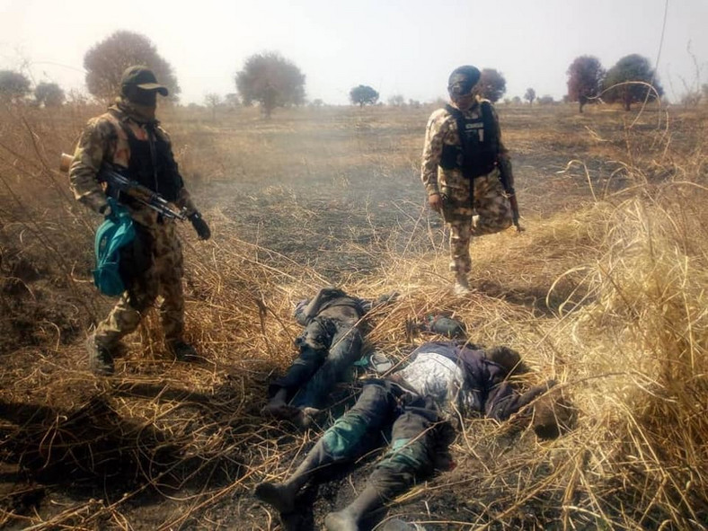 Nigerian soldiers stand over the corpses of neutralised Boko Haram terrorists [Facebook/HQ Nigerian Army]
