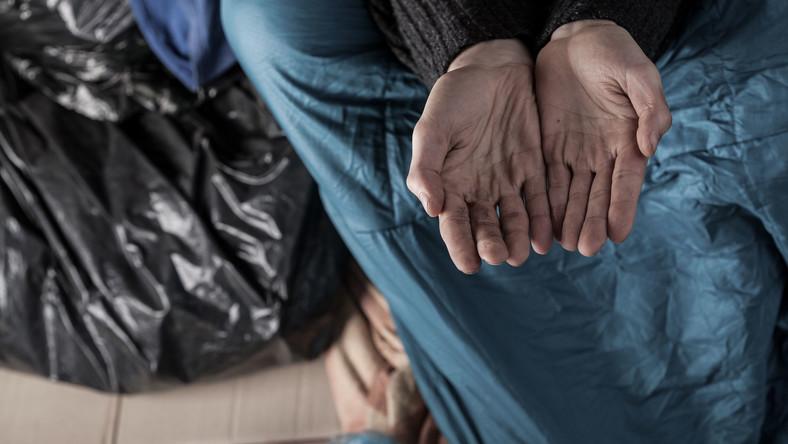 Biedny człowiek wyciągający ręce