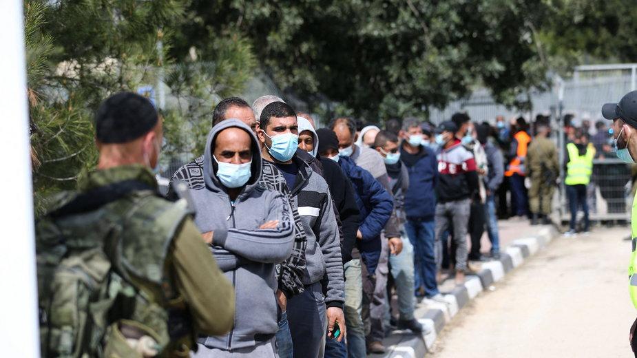 Palestyńscy robotnicy czekają w kolejce po pierwszą dawkę szczepionki Moderna w ośrodku szczepień utworzonym między Jerozolimą a Betlejem