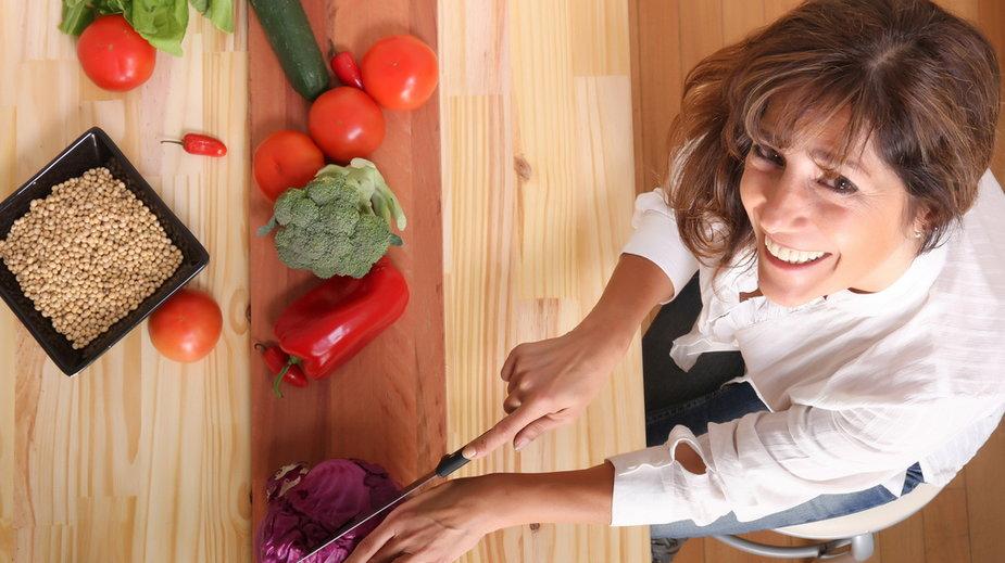 Kobieta w średnim wieku w kuchni kroi warzywa