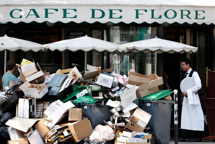 A waiter stands near a pile of rubbish bags in front of the Cafe de Flore in Paris during a strike of garbage collectors and sewer workers of the city of Paris to protest the labour reforms law proposal