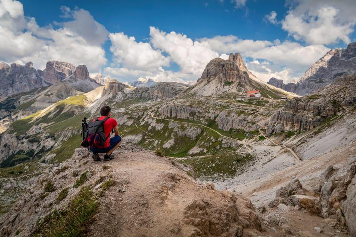 Man traveler hiking alone in breathtaking landscape of Dolomites mountains in summer in Italy.