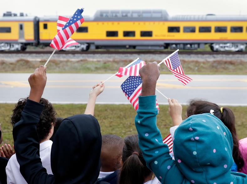 Students from Salyer Elementary School wave flags at the train.