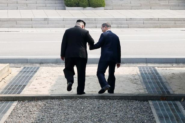 Najwyższy przywódca Korei Północnej Kim Dzong Un i prezydent Korei Południowej Mun Jae-in trzymają się za ręce, przechodząc symbolicznie przez linię demarkacyjną w strefie zdemilitaryzowanej pomiędzy dwoma krajami