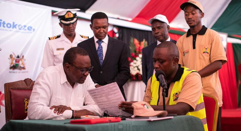 President Uhuru Kenyatta (left), being taken through the Huduma Namba registration form