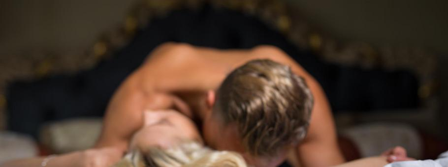 Man kissing womans neck while she is lying down