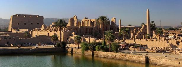 """W Karnaku znajduje się zespół świątyń wzniesionych w różnym czasie, poświęconych bogom tebańskim. Centralne miejsce zajmuje największa na świecie świątynia z salą kolumnową, tzw. """"Wielki Hypostyl"""" – świątynia Amona-Re. W 1979 Karnak został wpisany na Listę światowego dziedzictwa UNESCO."""