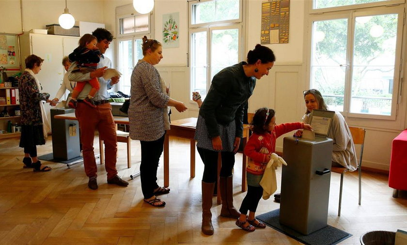 People cast their ballots during a vote on whether to give every adult citizen a basic guaranteed monthly income of 2,500 Swiss francs ($2,560), in a school in Bern