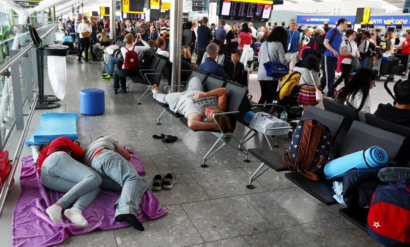 FILE PHOTO:People sleep next to their luggage at Heathrow Terminal 5 in London