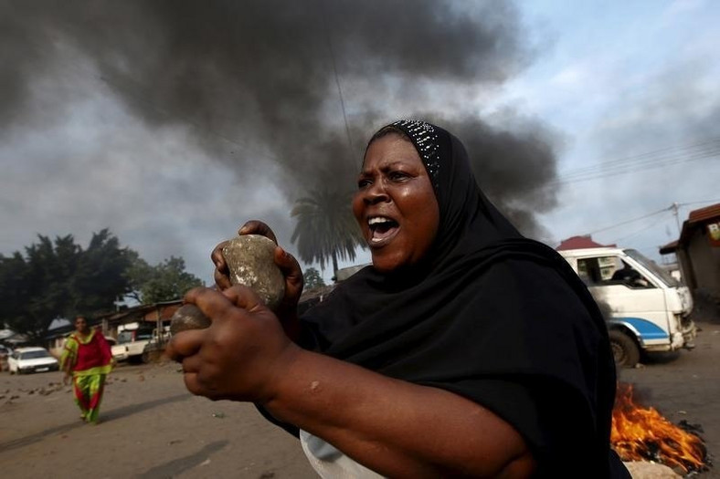 A woman gestures with stones during a protest against President Pierre Nkurunziza and his bid for a third term in Bujumbura May 26, 2015. REUTERS/Goran Tomasevic