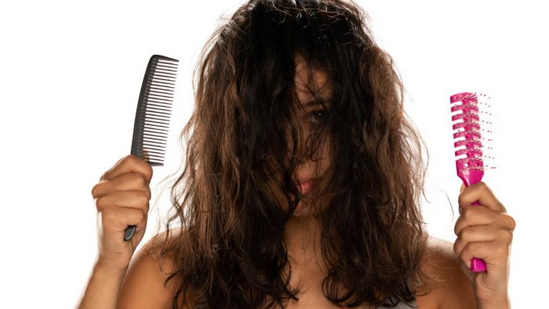 Kobieta próbuje uczesać napuszone włosy