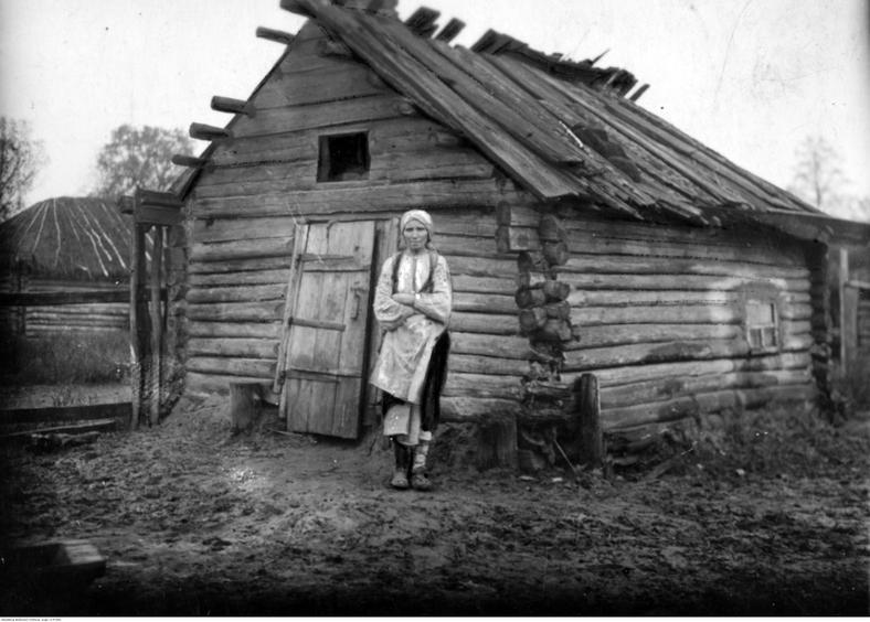 Kobieta z powiatu sarneńskiego na Polesiu Wołyńskim stoi na tle swojego chylącego się ku ziemi domu