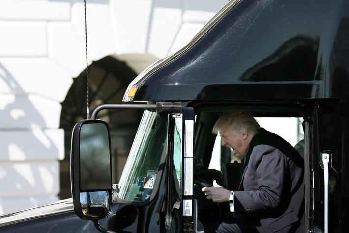 U.S. President Donald Trump reacts as he sits on a truck while he welcomes truckers and CEOs to atte