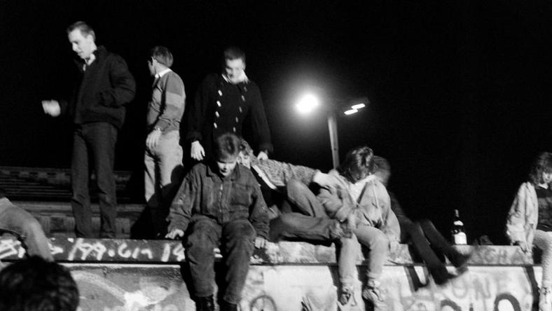 People from West Berlin climb over the Berlin Wall after its fall on November 9, 1989
