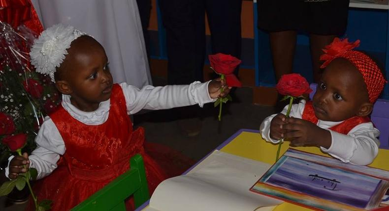 Formerly Conjoined twins babies Blessing and Favor exchange rose flowers at the Kenyatta National Hospital.