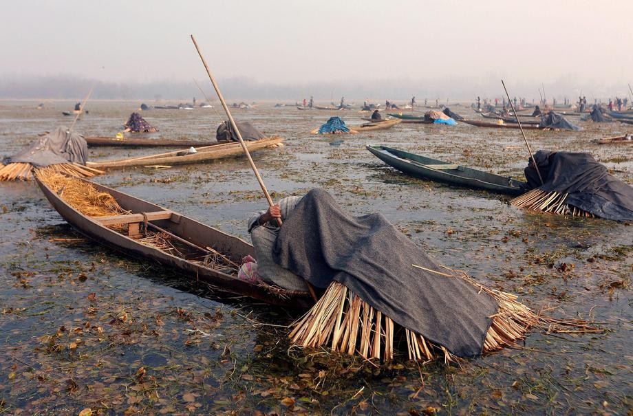 Fishermen cover their heads and part of their boats with blankets and straw as they wait to catch fi