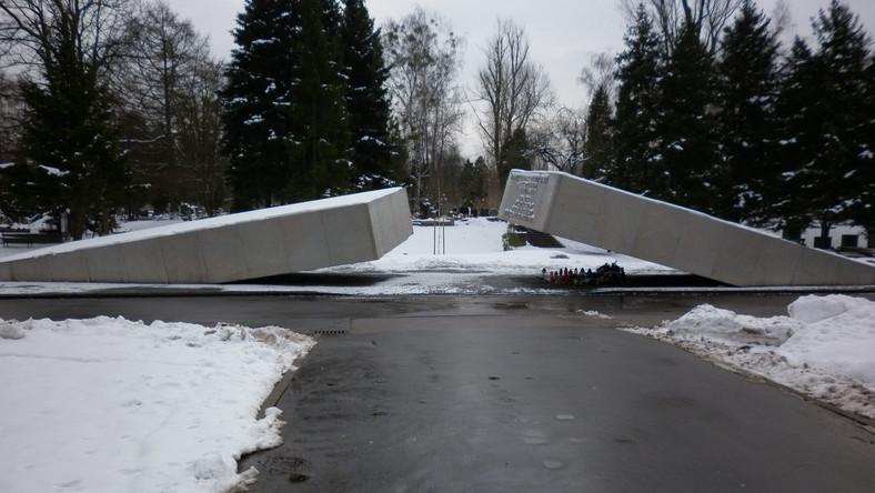 """Pomnik znajdujący się na Cmentarzu Wojskowym na Powązkach w Warszawie, zaprojektowany przez artystę rzeźbiarza Marka Moderaua, upamiętniający ofiary katastrofy polskiego Tu-154 w Smoleńsku, odsłonięty 10 listopada 2010 roku. Główny element monumentu to dwa żelbetowe prostopadłościany z okładzinami z białego kamienia. Oba prostopadłościany są umieszczone względem siebie w sposób, który sugeruje przełamanie jednej bryły, zapadającej się w ziemię. W miejscu """"przełamania"""", na bocznej ścianie jednego z prostopadłościanów, znajduje się lista 96 ofiar katastrofy w Smoleńsku, a po przeciwnej stronie, na bocznej ścianie drugiego prostopadłościanu, napis: """"PAMIĘCI 96 OFIAR KATASTROFY LOTNICZEJ POD SMOLEŃSKIEM 10 KWIETNIA 2010 ODDALI ŻYCIE W SŁUŻBIE OJCZYZNY W DRODZE NA OBCHODY 70 ROCZNICY ZBRODNI KATYŃSKIEJ"""""""