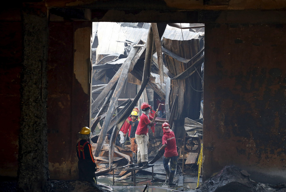 Workers remove debris in a gutted slipper factory in Valenzuela