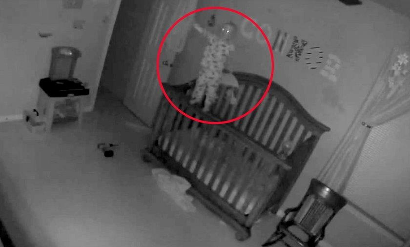 Dziecko balansuje na barierce łóżeczka