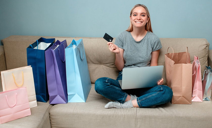 Online shopping at home. Young happy woman with credit card is ready to Singles day on a sofa near s