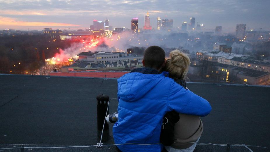 Słynne zdjęcie Pawła Supernaka z PAP. Obejmująca się para obserwuje z dachu uczestników Marszu Niepodległości 2014