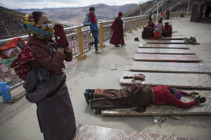 Ethnic Tibetan woman, carrying her baby on the back, prays at a monastery above the Larung Wuming Bu