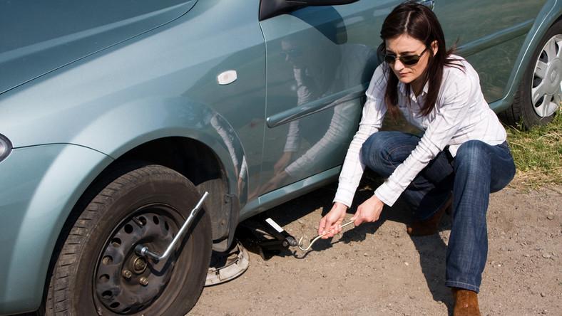Kobieta stara się zmienić uszkodzone koło w samochodzie