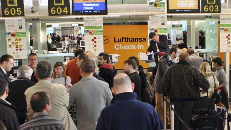 Pasażerowie próbują odprawić się przy stanowisku niemieckich linii Lufthansa na lotnisku El Prat w Barcelonie