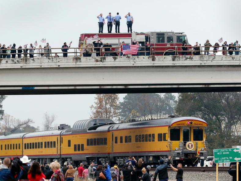 Firefighters pay their respects as the train rolls by.