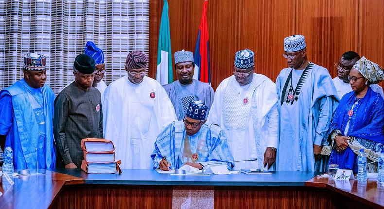 Government officials look as President Buhari sign the 2020 budget (Twitter @BashirAhmaad)