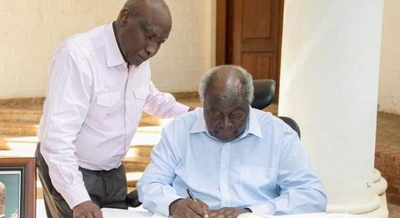 File imege of former President Mwai Kibaki signing a condolence book.