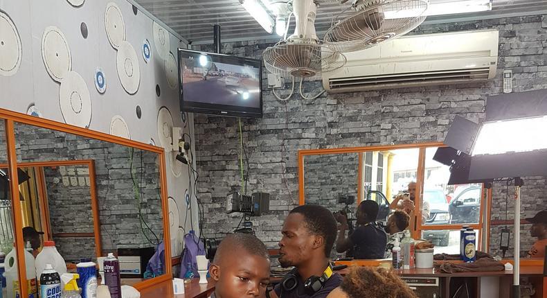 Lekan giving Pulse Tv's Chuey a haircut while Chris records them.