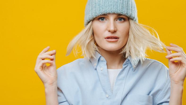 Kobieta ukrywa włosy pod czapką