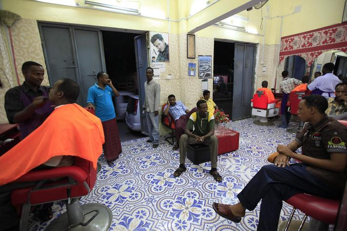 Men receive haircuts at a barber shop in Mogadishu October 3, 2013. Street lamps now brighten some o