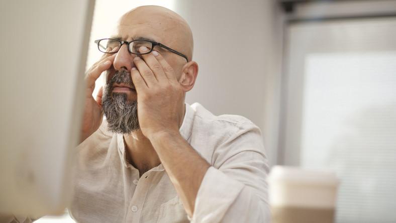 Mężczyzna przed komputerem ma zmęczony wzrok
