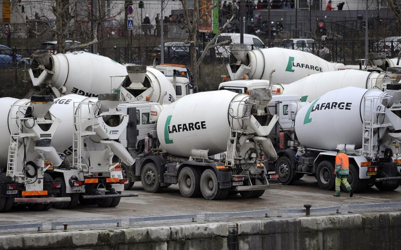 Cement mixer trucks sit parked on the quay side at a Lafarge SA  (Fabrice Dimier/Bloomberg)
