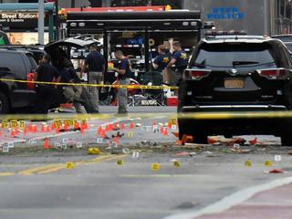 Evidence markers are seen on street around security officials near site of explosion in New York