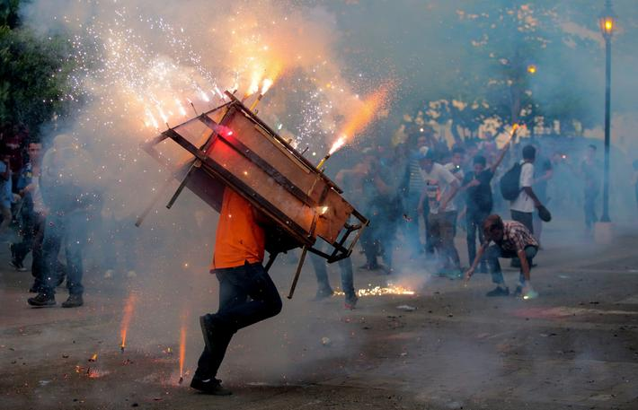 "A man runs with a ""toro encuetado"", a structure resembling a bull and emitting exploding firecracker"