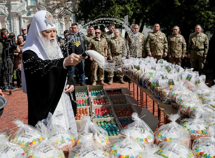 Metropolitan Filaret, the head of one of Ukraines Orthodox churches, sprinkles holy water during a