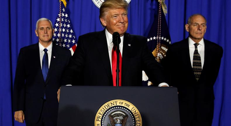 President Donald Trump (C), flanked by Vice President Mike Pence (L) and Homeland Security Secretary John Kelly (R), delivers remarks at Homeland Security headquarters on January 25, 2017.