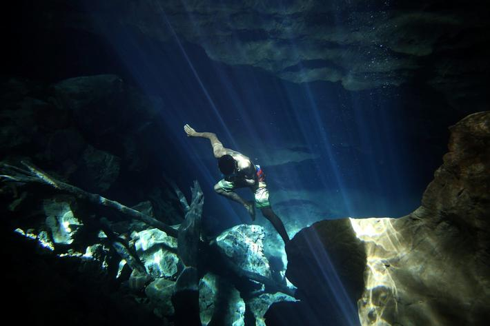 A worker of the cavern of Poco Azul (Blue well) dives to search for tourist dropped belongings, ahea