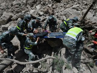 Chinese paramilitary police carry a survivor after an earthquake in Jiuzhaigou county